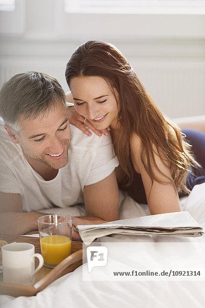 Paar liest Zeitung im Bett