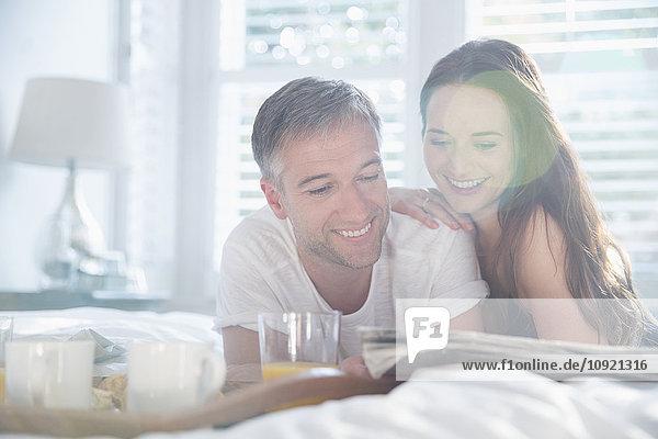 Lächelndes Paar liest Zeitung im sonnigen Schlafzimmer