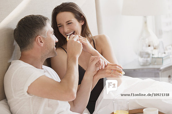 Lachendes Paar beim Frühstück im Bett