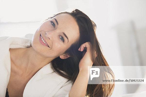 Portrait lächelnde Frau  die sich mit der Hand im Haar lehnt