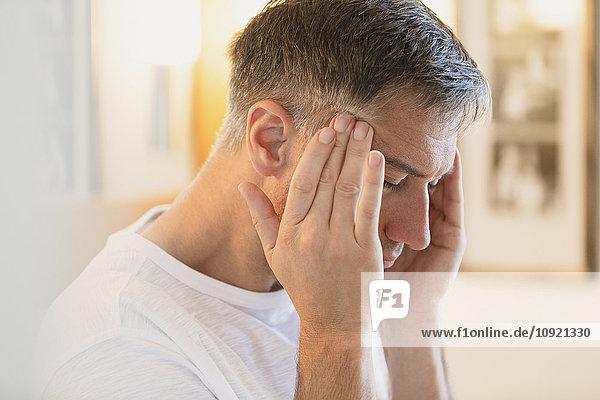 Mann mit Kopfschmerzen und reibender Schläfe