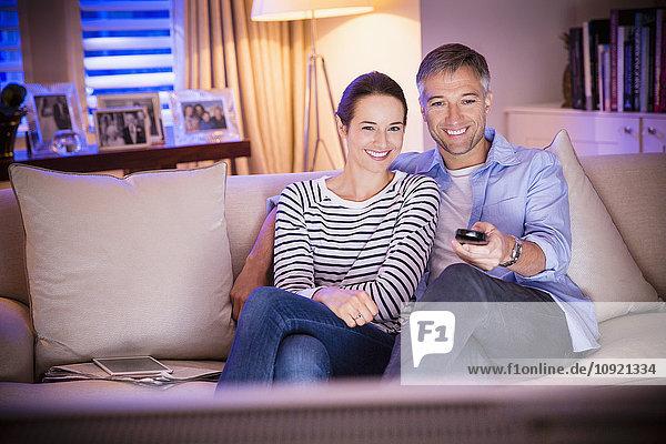 Lächelndes Paar beim Fernsehen im Wohnzimmer