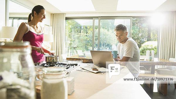 Paar Kochen und Arbeiten am Laptop in der Morgenküche