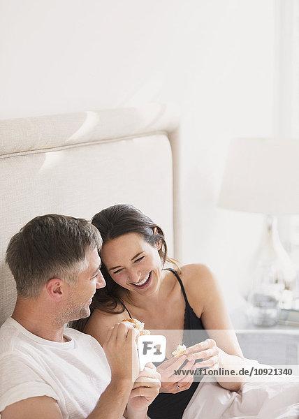 Lachendes Paar beim Essen im Bett
