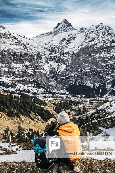 Paar mit Blick auf die verschneite Bergwelt  Grindelwald  Schweiz