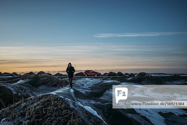 Mann auf eisigen Hügeln in abgelegener Landschaft  Hofn  Island