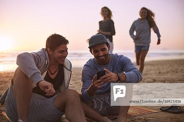 Freunde  die mit dem Handy am Strand bei Sonnenuntergang SMS schreiben.