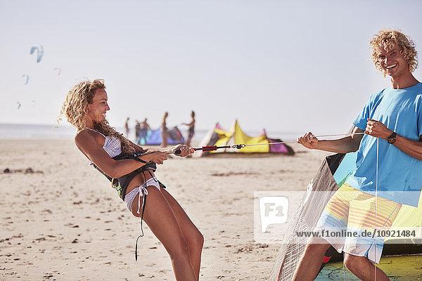Verspieltes Paar beim Kitesurfen am sonnigen Strand