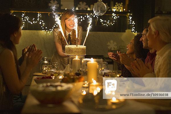 Frau serviert Weihnachtskuchen mit Wunderkerzenfeuerwerk an die klatschende Familie