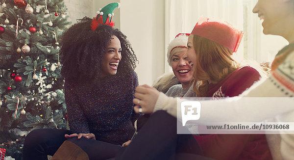 Freunde beim Reden und Lachen am Weihnachtsbaum
