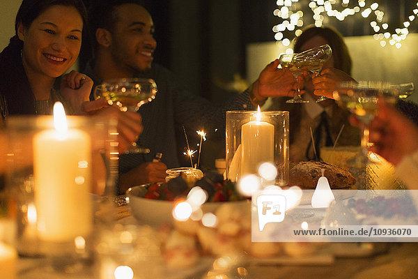 Freunde toasten Champagnergläser bei Kerzenschein am Weihnachtstisch
