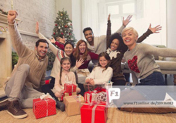 Portrait begeisterte Familie und Freunde mit Weihnachtsgeschenken im Wohnzimmer