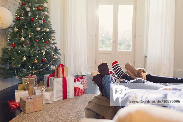 Entspannte Familie in Socken mit Füßen in der Nähe des Weihnachtsbaums