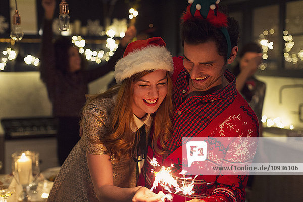 Verspieltes Paar mit weihnachtlichen Wunderkerzen