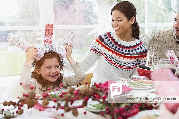 Verspieltes Mädchen mit Weihnachtsgebäck auf dem Kopf am Tisch