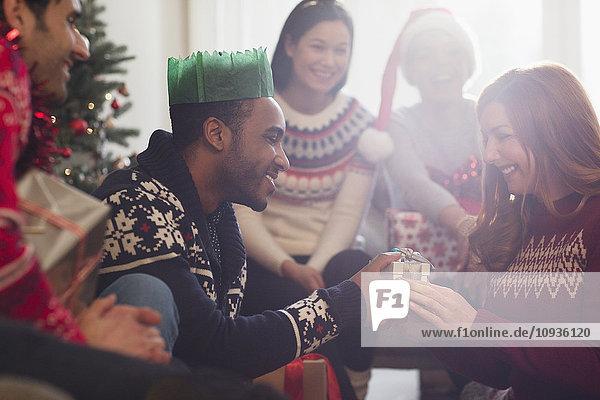 Freunde sehen zu  wie ihr Freund der Freundin ein Weihnachtsgeschenk macht.