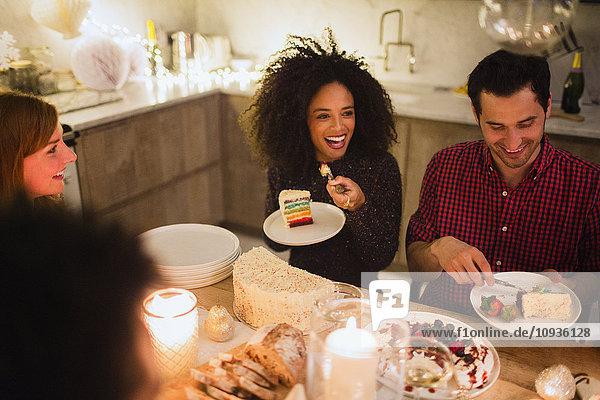 Freunde essen Kuchen am Tisch bei Kerzenlicht