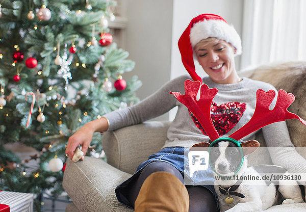 Frau auf Sofa sitzend mit Hund in Rentiergeweih am Weihnachtsbaum