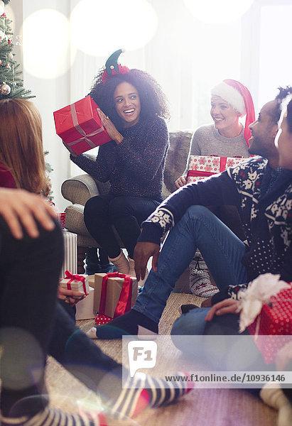 Freunde eröffnen Weihnachtsgeschenke im Wohnzimmer