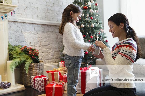 Mutter und Tochter eröffnen Weihnachtsgeschenk im Wohnzimmer