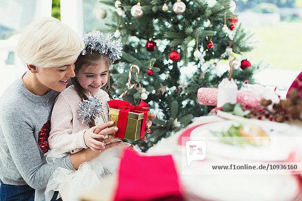 Lächelnde Mutter und Tochter mit Weihnachtsgeschenk