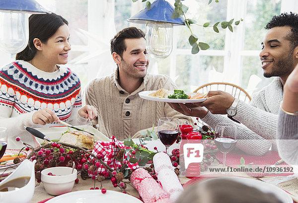 Frau serviert Truthahn beim Weihnachtsessen