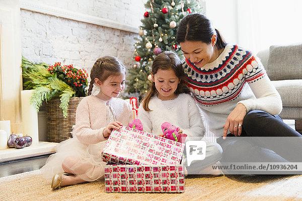 Mutter und Töchter eröffnen Weihnachtsgeschenke auf dem Wohnzimmerboden