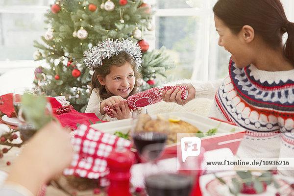 Mutter und Tochter ziehen Weihnachts-Cracker am Esstisch