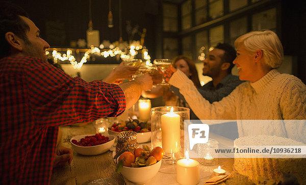 Freunde toasten Champagnergläser bei Kerzenschein Weihnachtsfeier