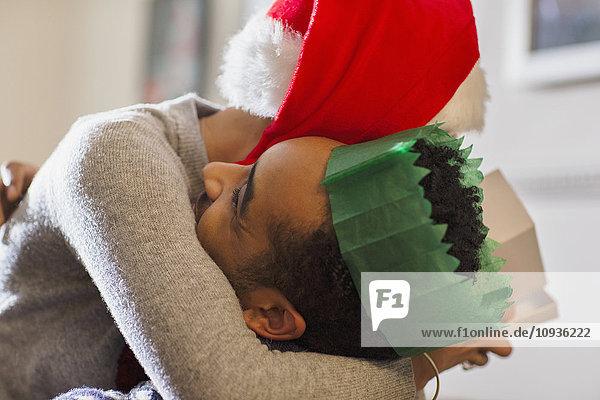 Liebespaar in Papierkrone und Weihnachtsmann-Hutumarmung