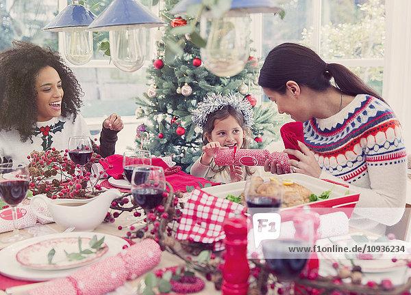 Mutter und Tochter ziehen beim Abendessen einen Weihnachtsknacker.