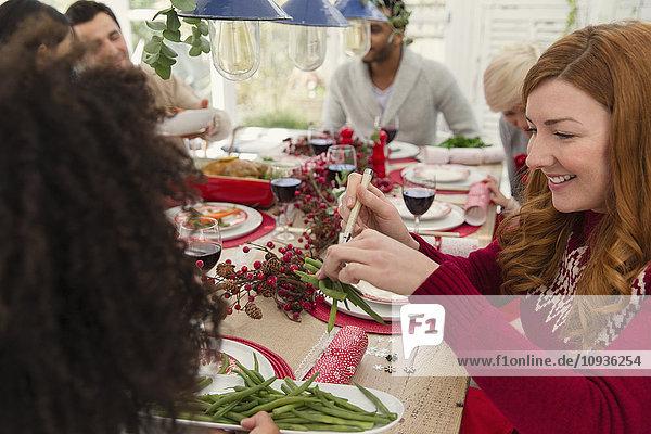 Frau serviert grüne Bohnen zum Weihnachtsessen