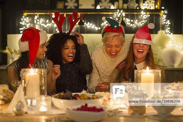 Lachende Freunde beim Weihnachtsessen bei Kerzenschein