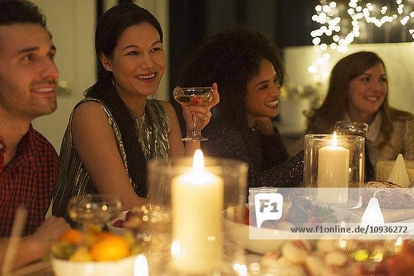 Lächelnde Freunde trinken Champagner bei Kerzenlicht Weihnachtsessen