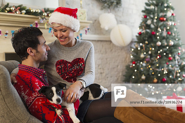 Liebespaar mit Hund entspannt im Wohnzimmer mit Weihnachtsbaum