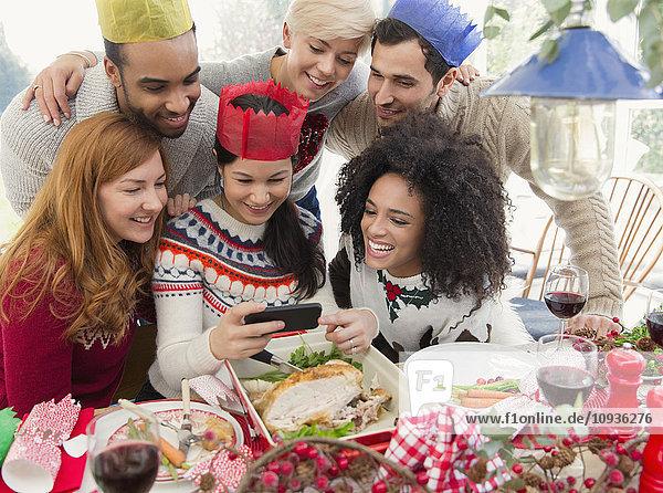 Freunde  die Papierkronen tragen und Selfie zum Weihnachtsessen nehmen