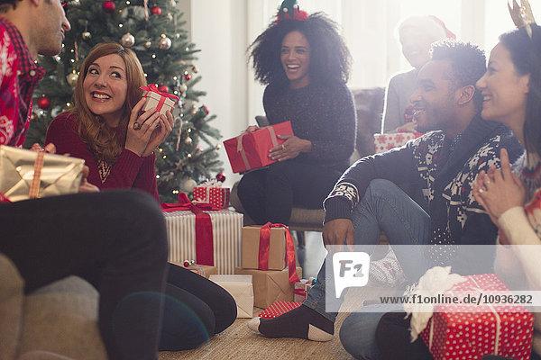 Freunde beobachten verspielte Frau schüttelt Weihnachtsgeschenk