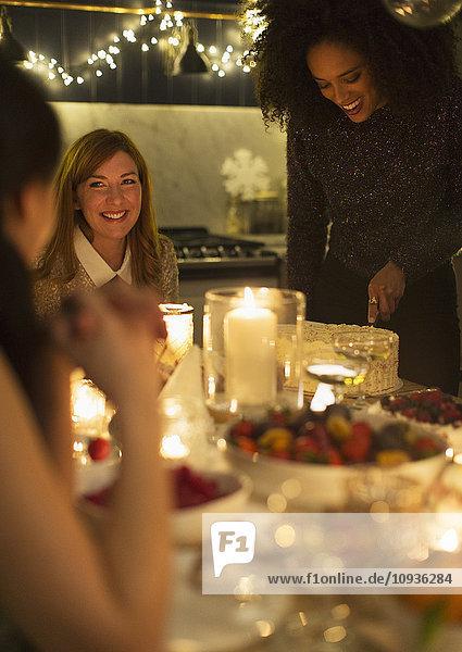 Lächelnde Freunde bei Kerzenschein und Weihnachtsdessert