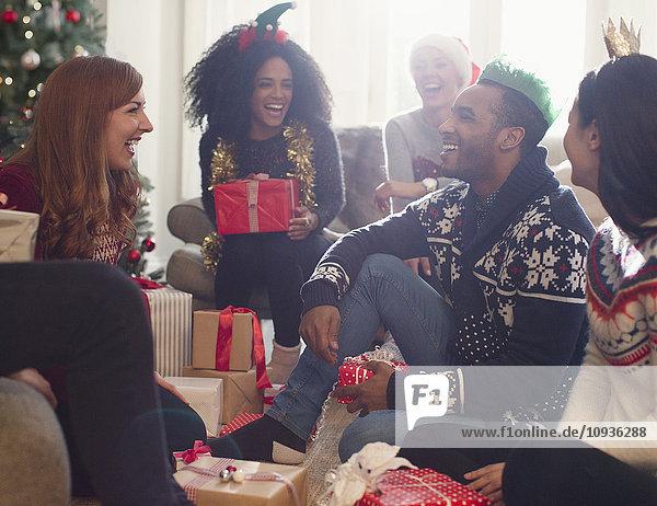 Lachende Freunde eröffnen Weihnachtsgeschenke im Wohnzimmer