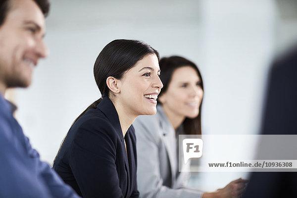 Lächelnde Geschäftsfrau beim Zuhören im Meeting