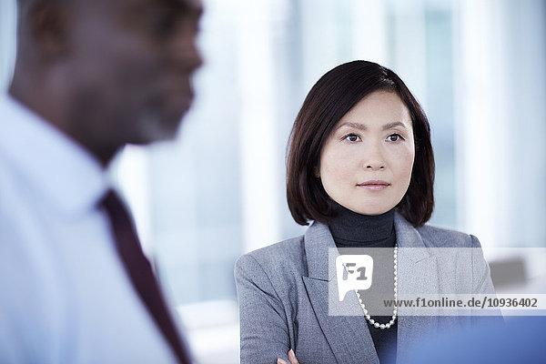 Seriöse Geschäftsfrau beim Zuhören im Meeting