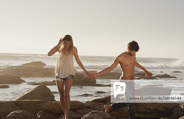 Young couple holding hands and walking on ocean rocks