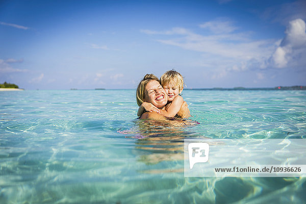 Enthusiastic mother hugging son in tropical ocean