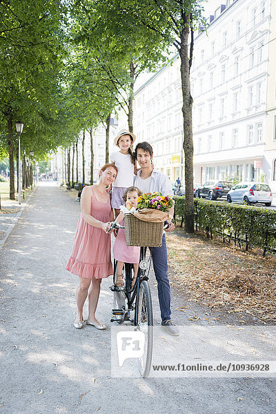 Family with two children pushing bicycle in city