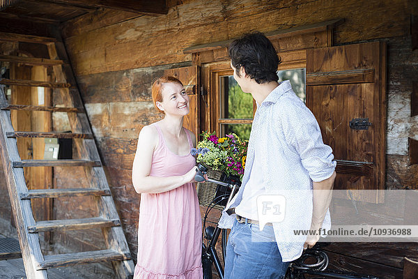 Happy couple in front of log cabin