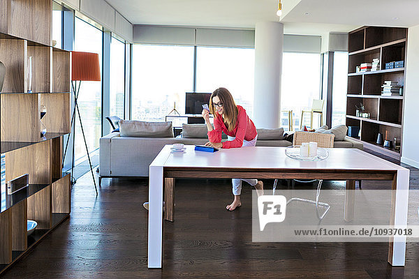 Woman in apartment shopping online with digital tablet