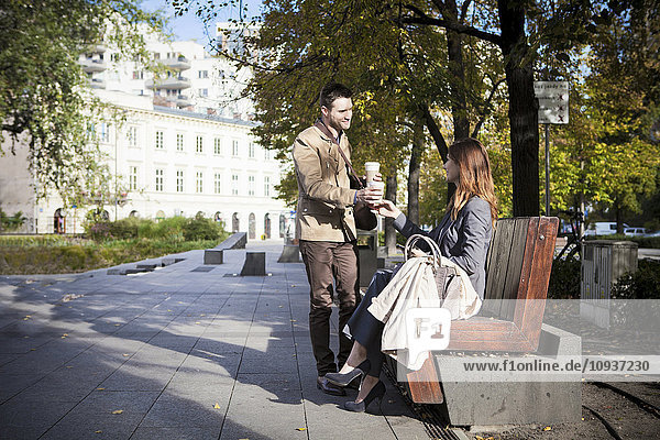 Two business people having a cup of coffee in park