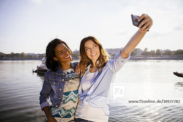 Two women making a selfie with smart phone