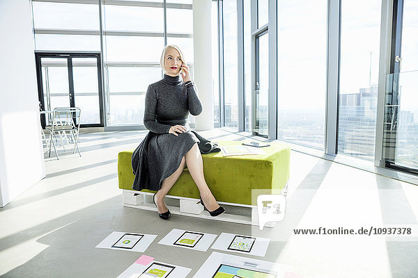 Female architect using mobile phone in modern office