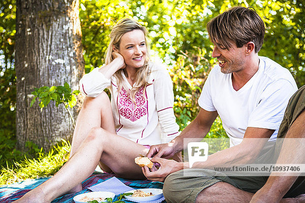 Young couple barbecuing on the riverside  foothills of the Alps  Bavaria  Germany